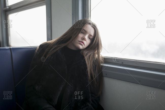 Young woman wearing black fur coat on train