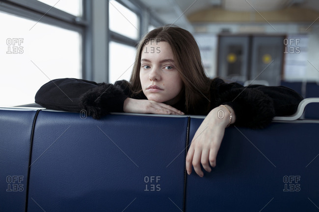 Young woman leaning on blue seat on train