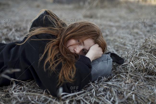 Teenage girl lying on bag in field