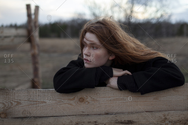 Teenage girl leaning on wooden fence