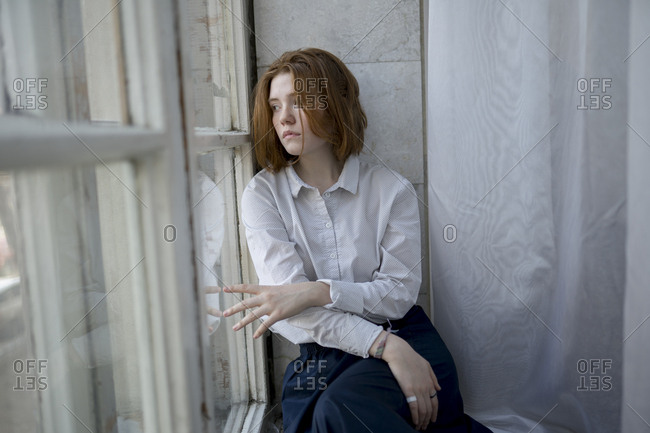 Young woman wearing white shirt on window sill