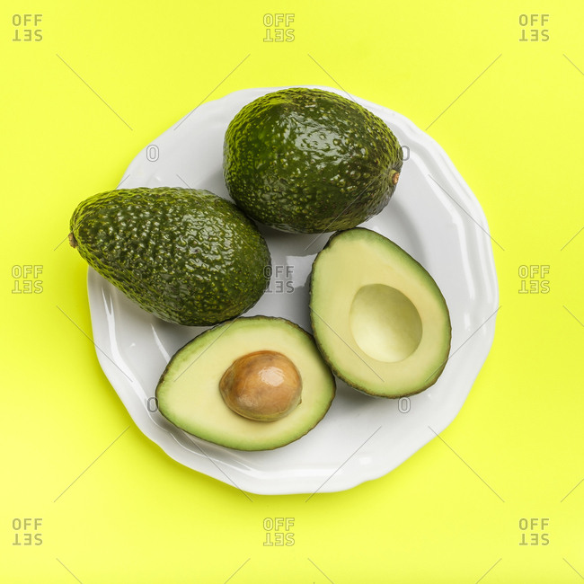 Plate of avocados on green surface