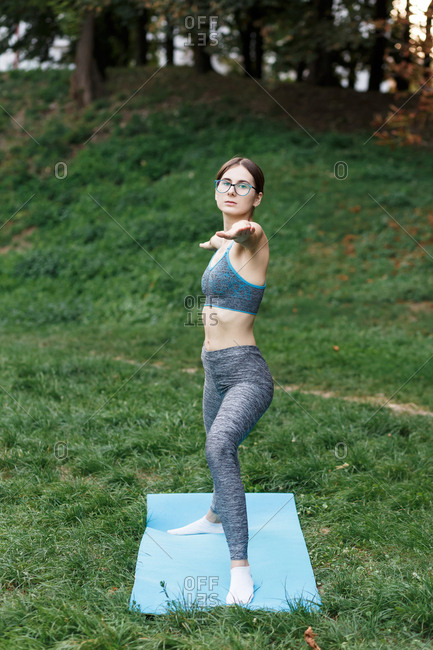 A relaxed girl is doing yoga on a mat in the park