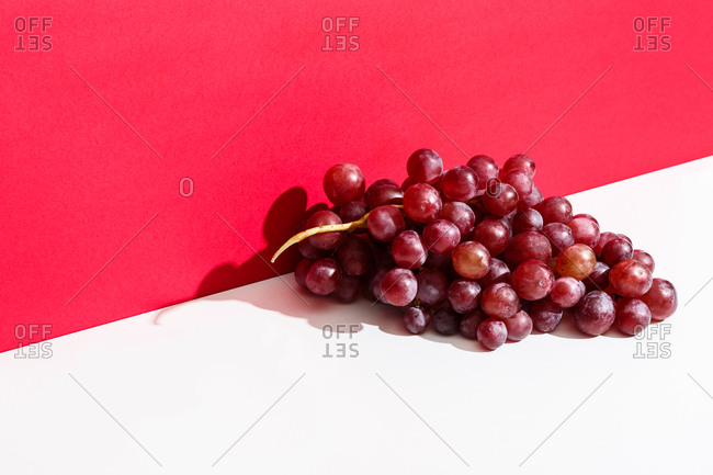 Bunch of red grapes against a red wall