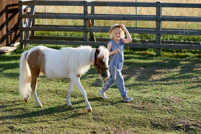 Stylish pretty little girl enjoying walk with cute pony on farm on bright summer  day