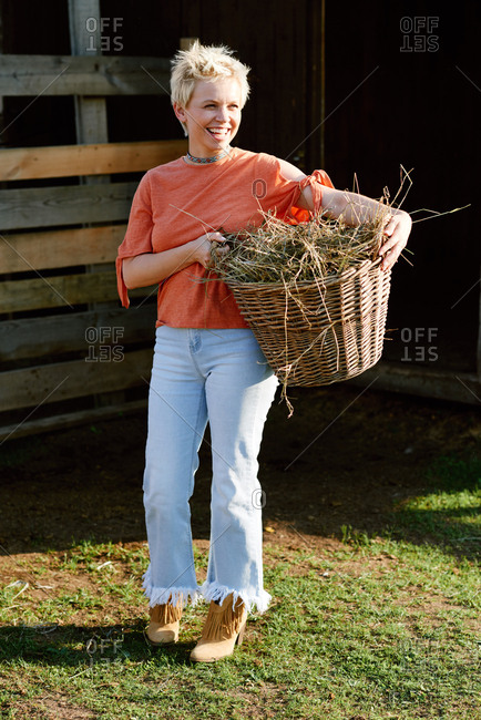 Young fashionable blond-haired woman holding basket with hay, looking away and smiling happily