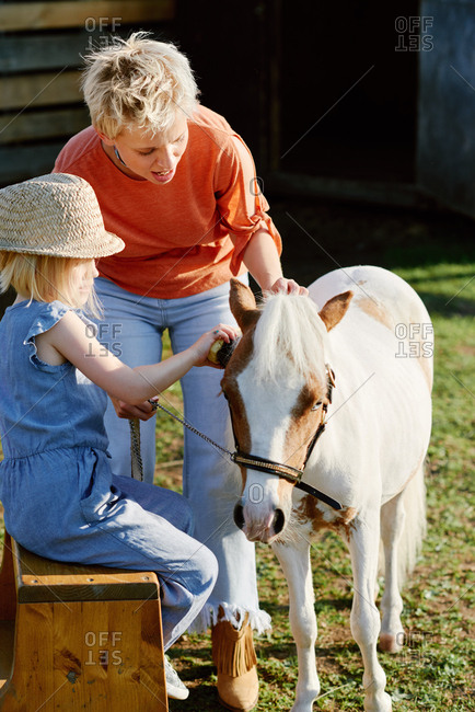 Young blond woman and her stylish little daughter grooming cute pony on farm on warm summer day