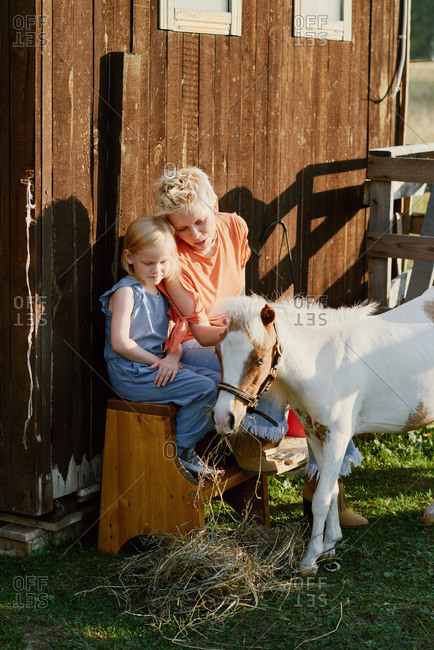 Young blond woman and her little daughter spending time on pony farm, resting on bench, feeding and petting cute miniature horse