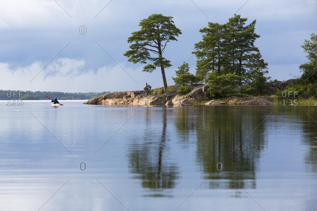 Sweden, garden of skerry / skargard, single kayakist in scenery