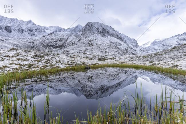 Austria, tyrol, the stubai alps, neustift, mirroring of the alpeiner mountains in a small lake near the franz-senn-h�tte (hut)