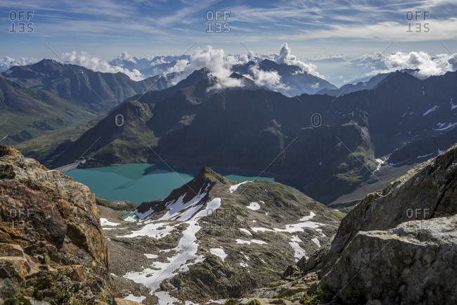 Austria, tyrol, the stubai alps, kuhtai, view of the sulzkogel on the finstertaler speicher (reservoir) and the surrounding mountains in a sunny summer morning