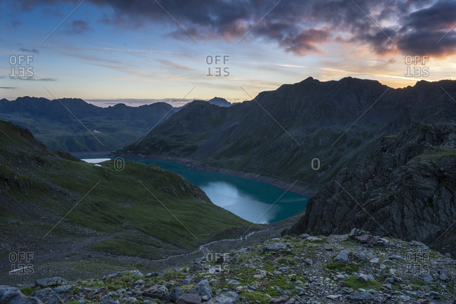Austria, tyrol, the stubai alps, kuhtai, sunrise behind the finstertaler speicher (reservoir)