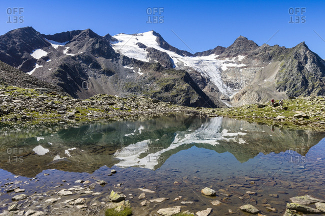 Austria, tyrol, the stubai alps, neustift, mirroring of the wilde freigers in a small lake with passing hikers