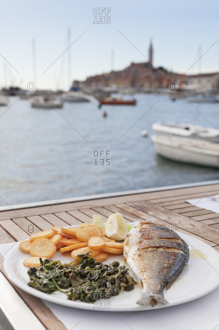 Plate with fish, potatoes and spinach in a restaurant in the harbor of rovinj, istria, croatia