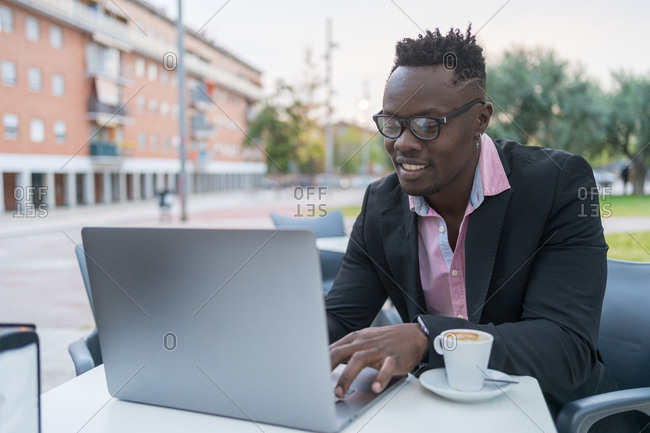 Happy black businessman working on a laptop sitting on a terrace