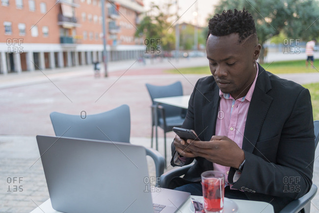 Black businessman laughs out loud as he makes a video call on his laptop sitting on a terrace