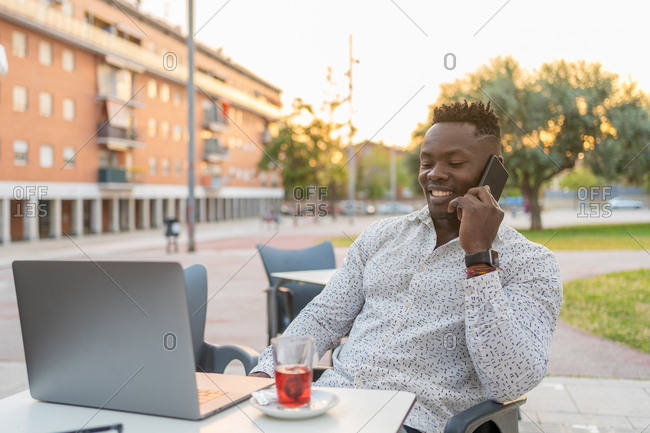 Happy black businessman talking on the phone sitting on a terrace