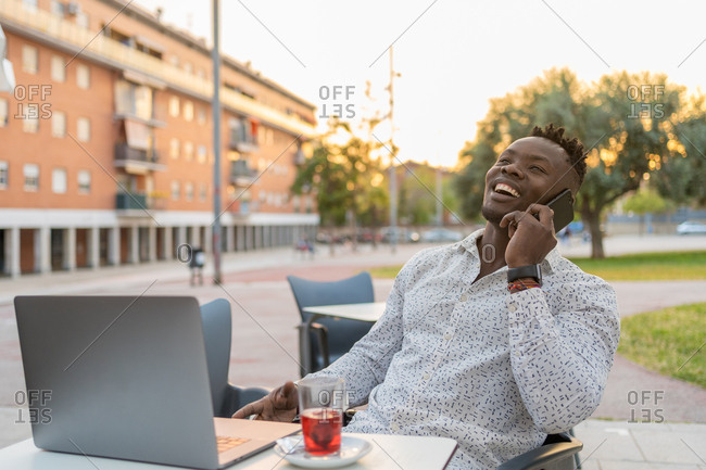 African businessman laughs as he talks on his cell phone sitting on a terrace