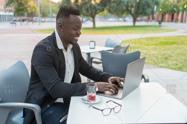 Happy black businessman checking his email on a terrace