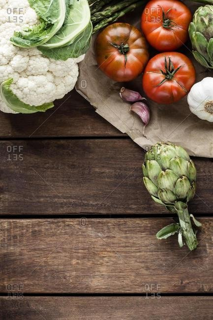 Cauliflower, artichokes, asparagus, garlic and tomatoes on a wooden table