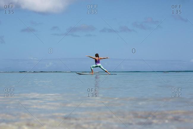 Woman doing yoga on a paddleboard, Oahu, Hawaii, USA