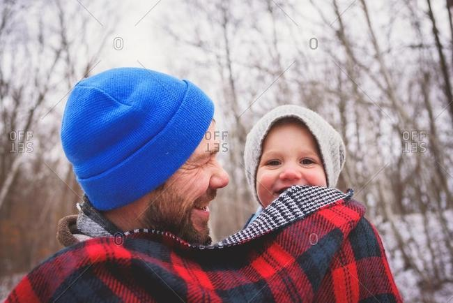 Portrait of a father carrying his baby son in a winter forest wrapped in a blanket