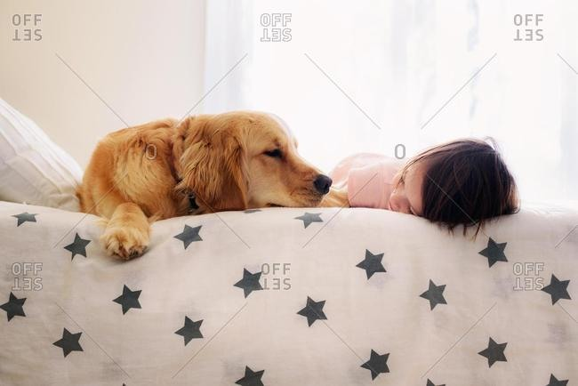 Smiling Girl lying on a bed next to a golden retriever dog