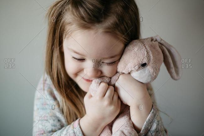 Smiling Girl cuddling a soft toy