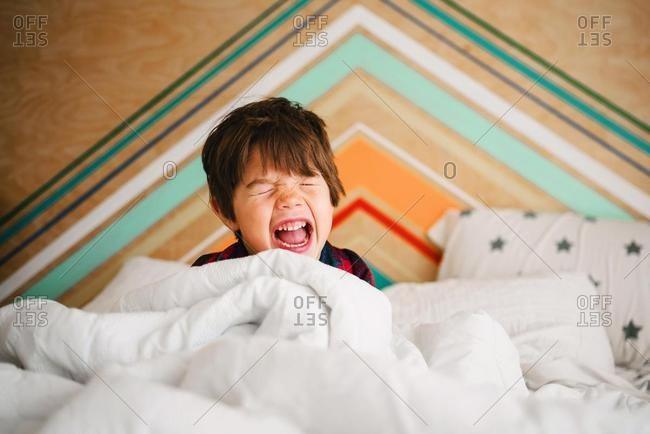 Boy sitting in bed having a tantrum