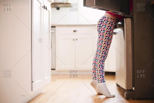 Girl looking for food in an open refrigerator in the kitchen