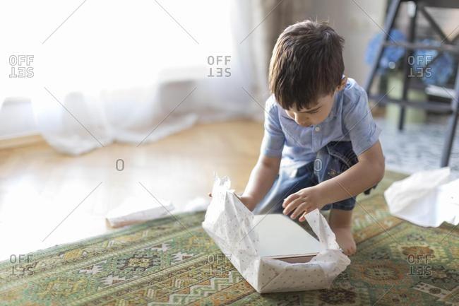 Boy sitting on floor unwrapping a birthday gift