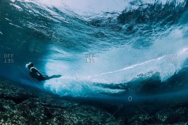 Man swimming underwater over a shallow reef, Kalapana, West Puna, Hawaii, USA