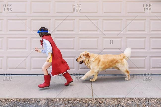 Girl dressed as a superhero running past a garage door with her dog