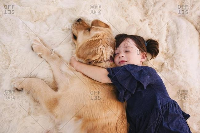Girl sleeping on a rug with her golden retriever dog