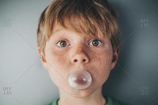 Portrait of a boy with freckles blowing a bubble gum bubble