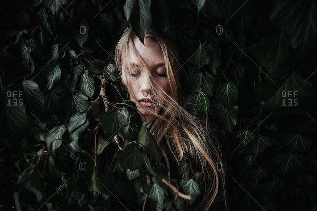 Portrait of a woman hiding in ivy