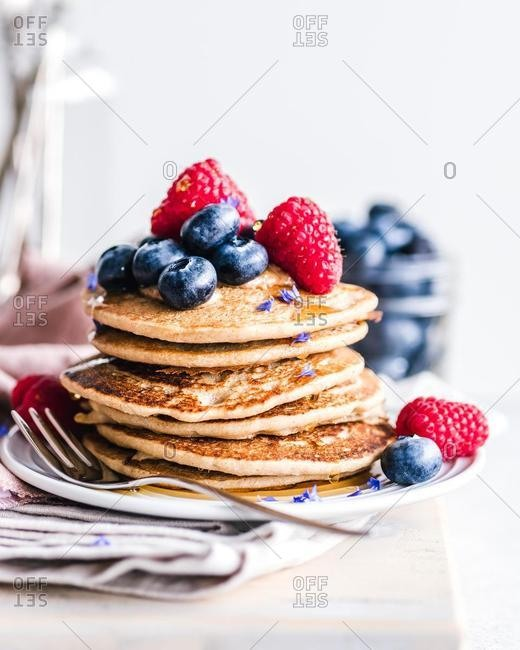 Stack of pancakes with blueberries, raspberries and maple syrup