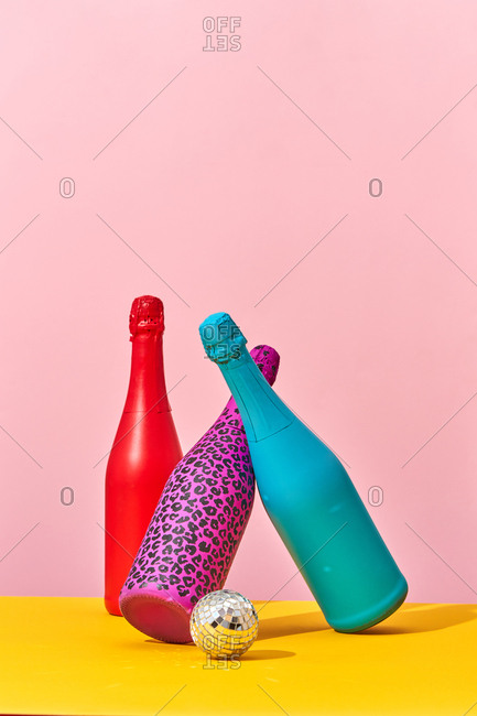 Painted bottles and a bright New Years disco ball on a duotone background