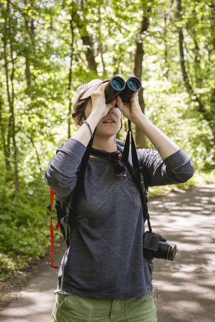 Hiker - looking through binoculars while standing in forest at Redwood National and State Parks