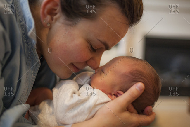Mother rubbing noses with baby boy at home