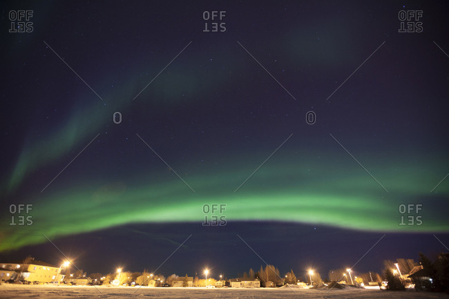 Idyllic view of aurora borealis over houses