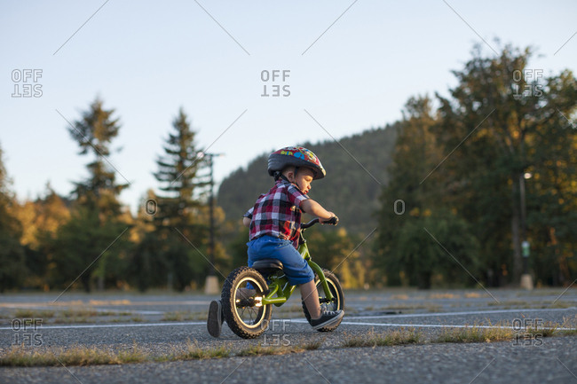 Full length of boy wearing bicycle helmet while cycling at park