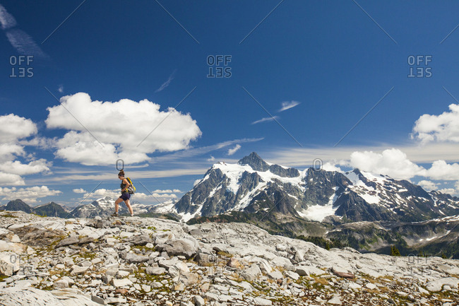 Mid distance view of female backpacker hiking against mountains and sky during winter at North Cascades National Park