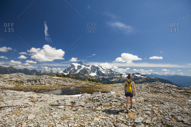 Rear view of female backpacker hiking against mountains and sky during winter at North Cascades National Park