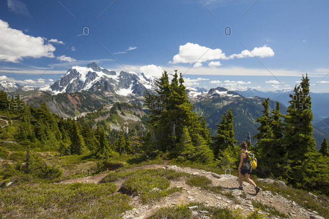 Full length of female hiker walking against mountains and sky during winter at North Cascades National Park