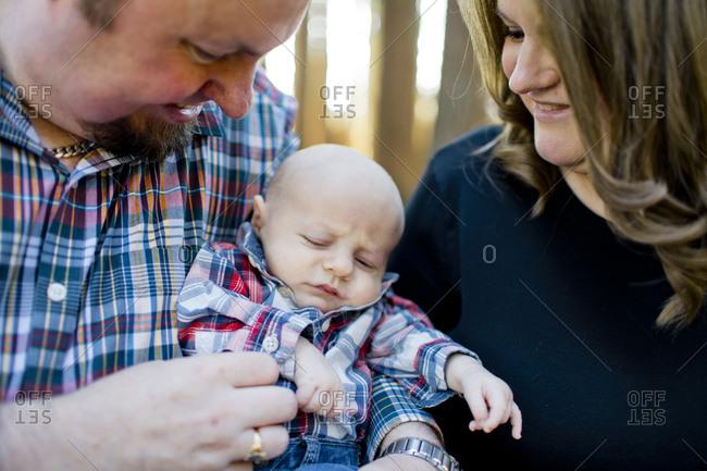 New parents hold their newborn son.