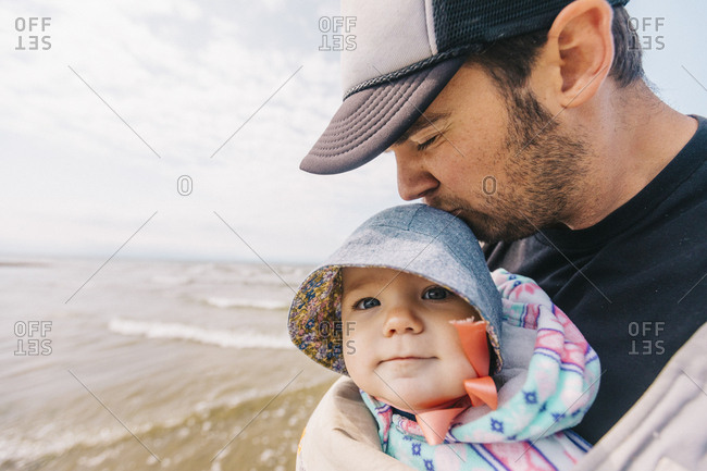 father kissing daughter in baby carrier at beach.