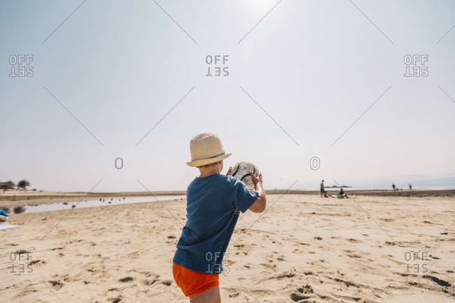 Young boy throwing ball at the beach.