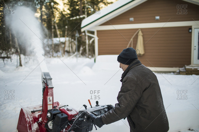 Side view of man snow blowing his driveway