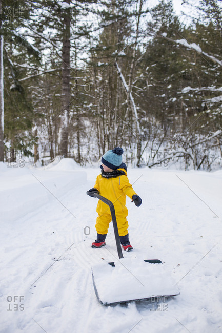 Toddler uses a large snow shovel to clear snow off the driveway.